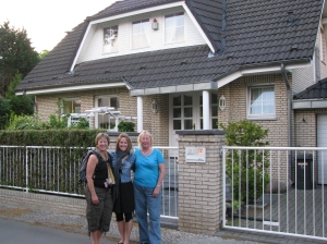 Three generations standing outside my grandma's former family home in 2009.  The original house (to the left) was bombed during the war.
