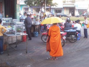 A barefooted monk collecting morning alms from the people.