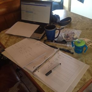 The state of my kitchen table these days: day book, lap top open to school calendars, coffee, sippy cup, school keys, and my beckoning workout DVDs.  Oh, and Sophie, because Charlee has four teeth now.